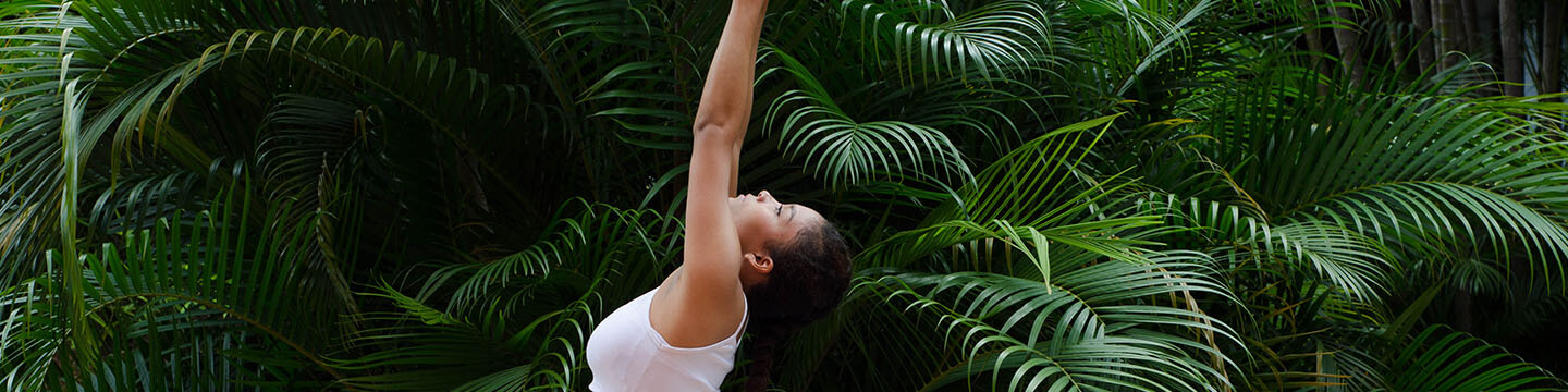 A woman in athletic clothes doing yoga poses in front of a wall of plants