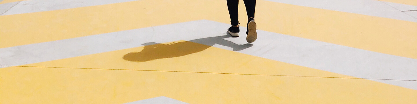 A woman wearing black athletic sneakers walking on a yellow striped concrete sidewalk