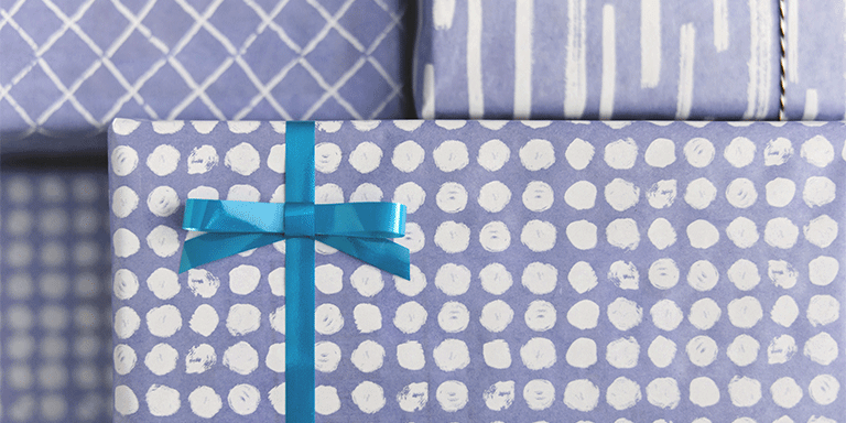 Close up of a present wrapped in purple polka dot wrapping paper with a blue bow