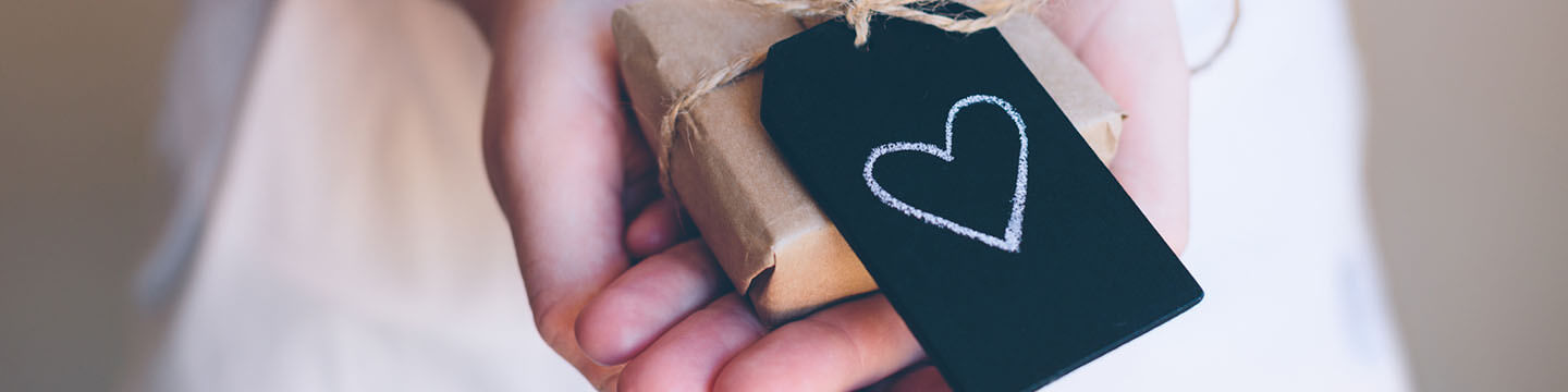 Woman holding a present wrapped in brown paper with a black tag with a white heart on it