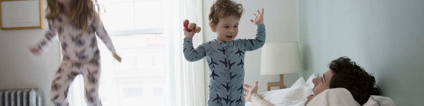 Two young children in pajamas jumping on their parents bed in the early morning