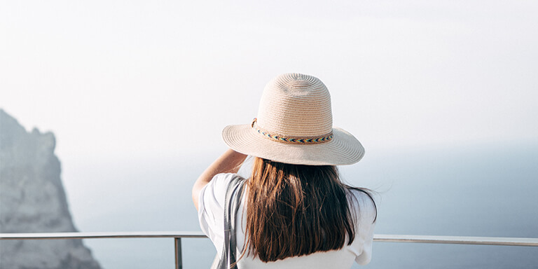 A woman in a sun hat talking a photo of the ocean and cliffside views