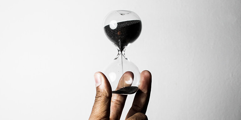 A hand holding up an hourglass with black sand against a white wall
