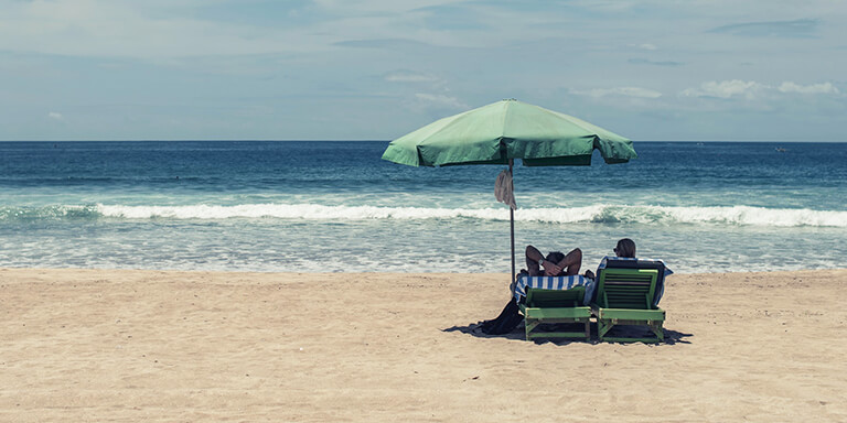 A couple sitting in beach chairs underneath an umbrella facing the ocean on an empty beach