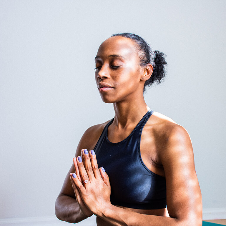 Women in black athletic clothing meditating with her palms pressed tightly together