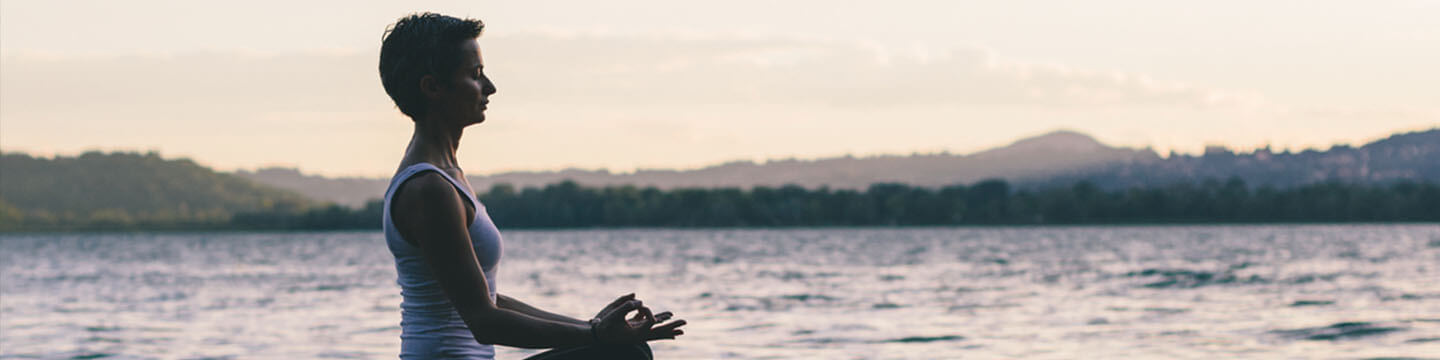 Woman wearing athletic clothes meditating on a dock on a lake at sunrise