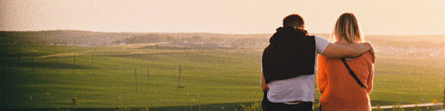 Man with his arm around a woman sitting on a ledge overlooking green fields at sunset