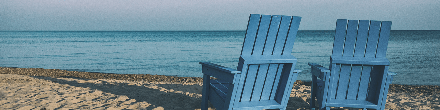 Two blue adirondack chairs on the beach facing towards the ocean
