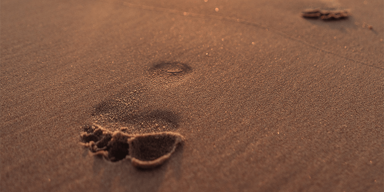 A pair of footprints in wet sand at the beach with a sunset