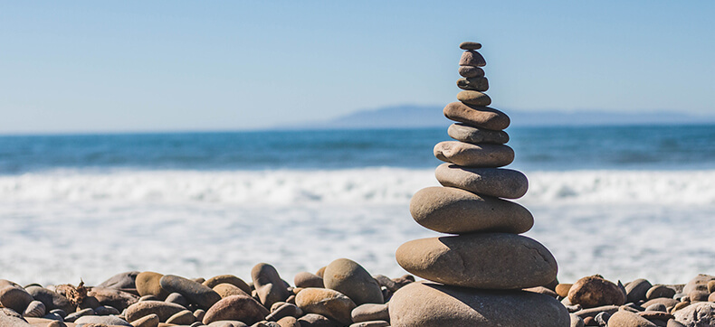 A cairn of beach rocks in front of the ocean