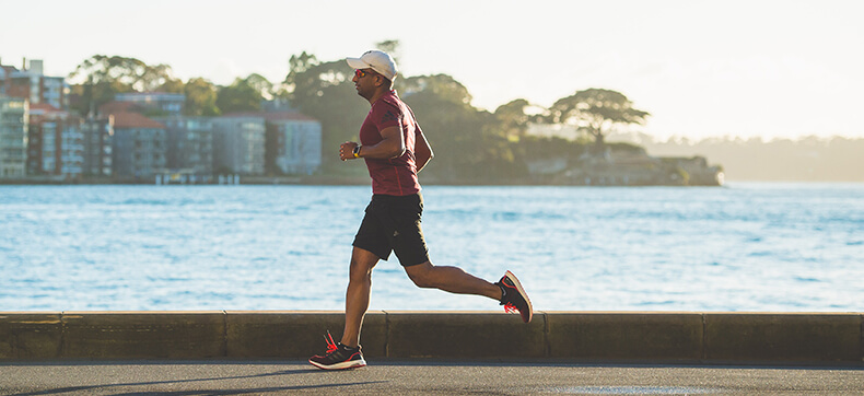 A man in athletic wear and a hat running along the edge of the waterfront