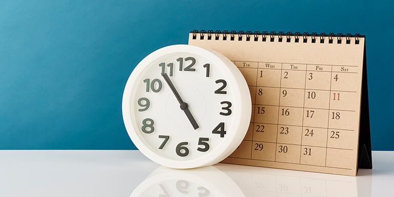 A white clock and a large construction paper calendar resting against a teal-colored wall