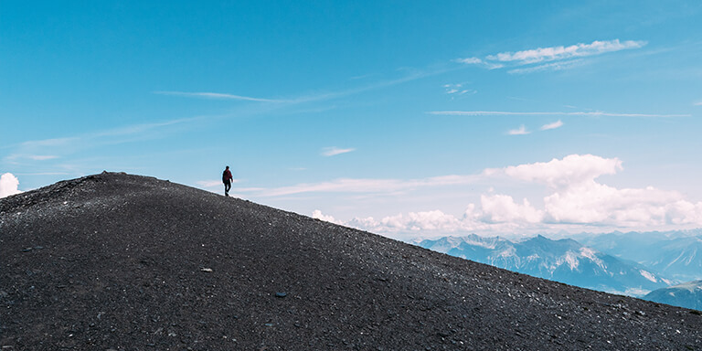 Solo person standing on the top of a mountain overlooking the rest of the peaks in a mountain range