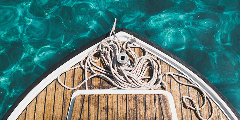 Overhead view of a coil of rope resting on the bow of a boat in clear turquoise water