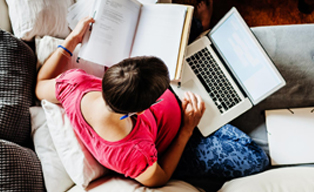 Overhead of a women sitting on a couch, working on her laptop and a notebook at the same time
