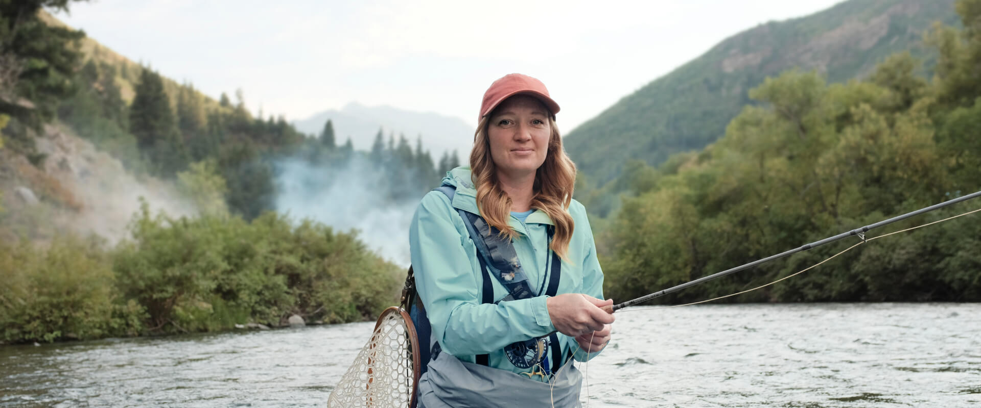 Woman in a hat and athletic clothes fly fishing in a river