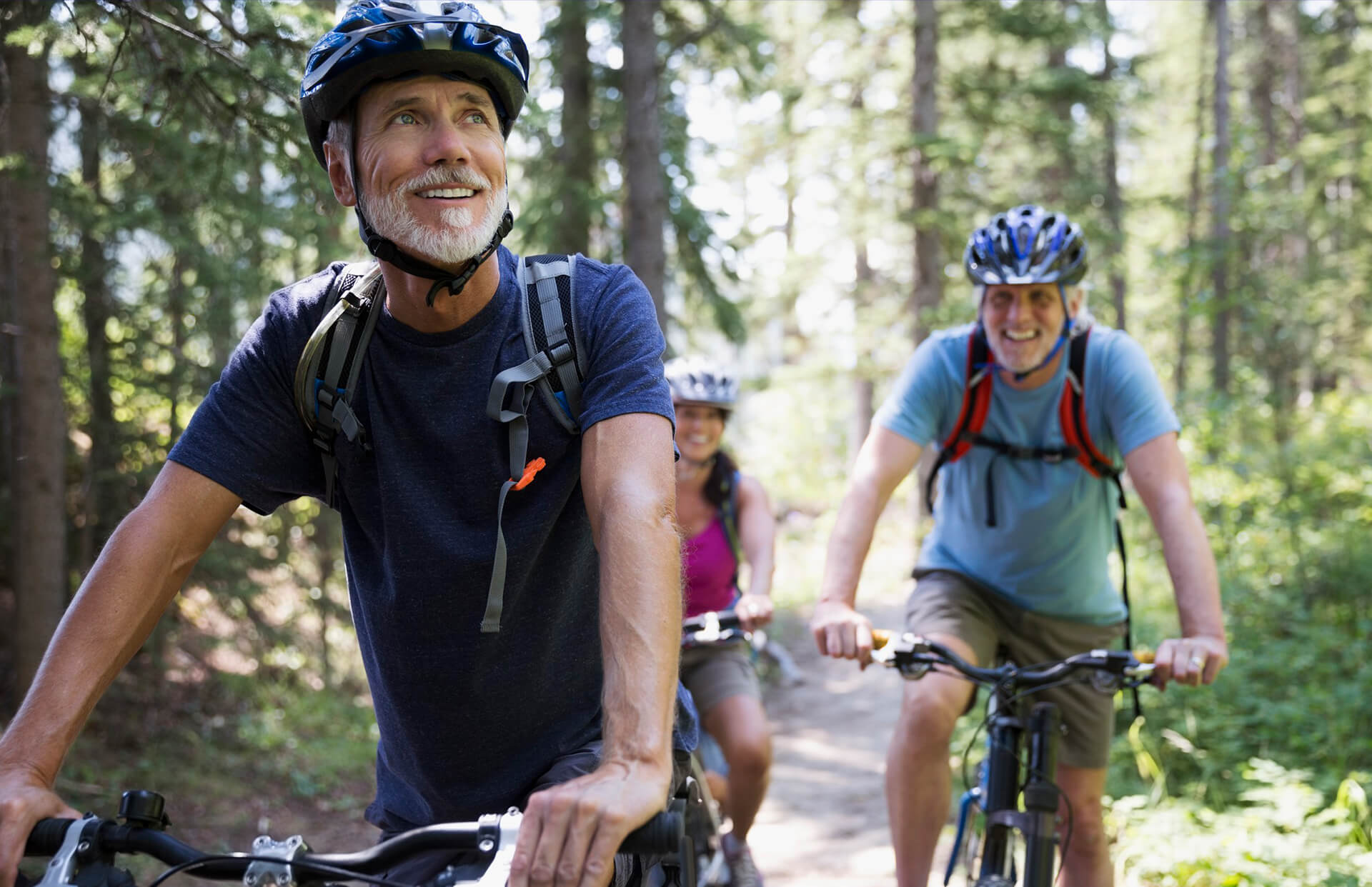 3 people in helmets riding their bikes through a forest trail
