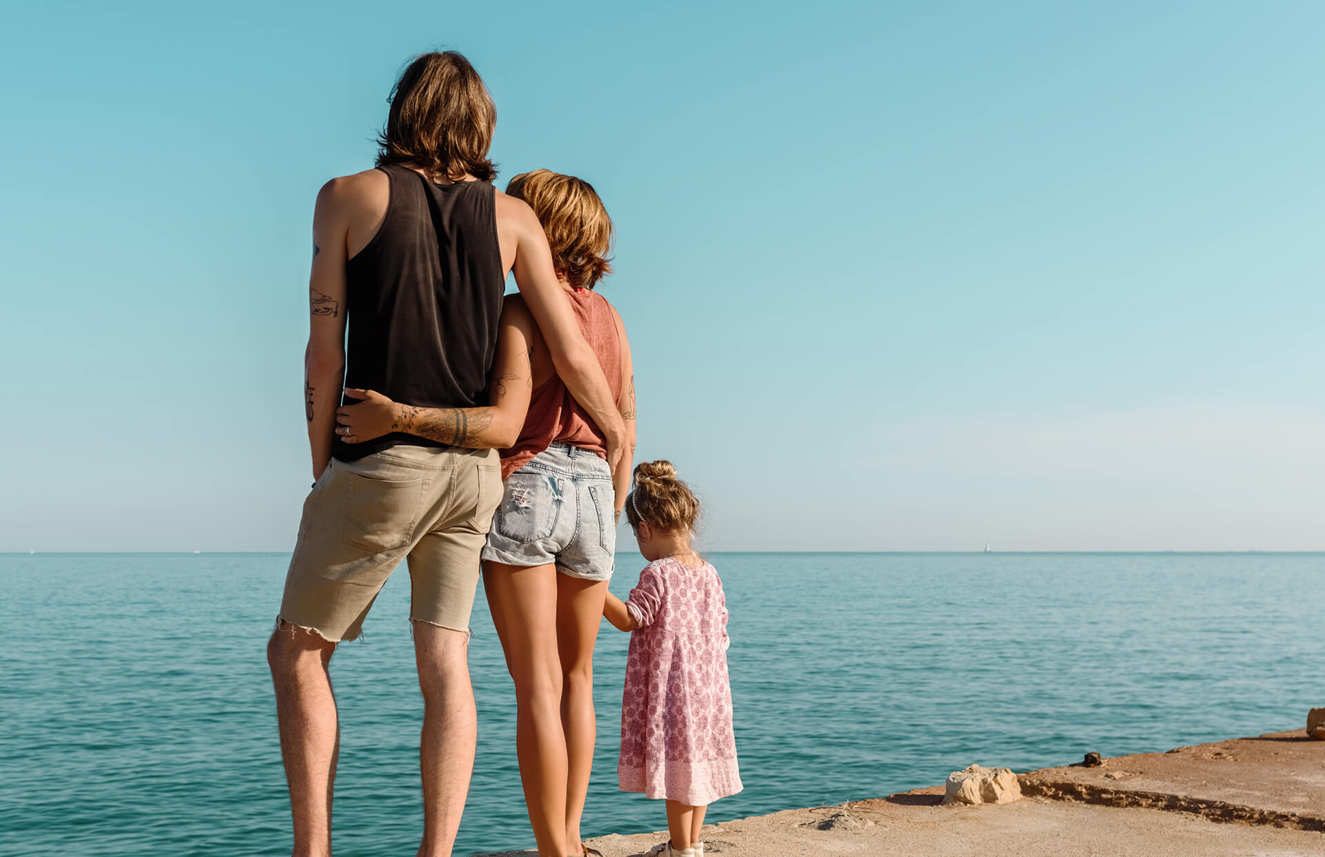Embracing couple with their young daughter standing on concrete seafront in sunlight